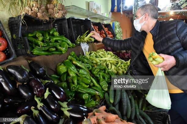 An Algerian man buys vegetables at a market on the outskirts of the capital Algiers during the Muslim holy month of Ramadan on April 25 2020 This...