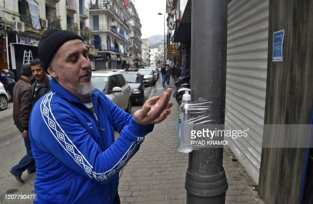 An Algerian man disinfects his hands with alcohol gel attached to a pole in Algiers' Bab elOued district on March 20 2020 A total of 82 cases of...
