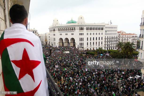 An Algerian man draped in a national flag watches as protesters gather for a demonstration against ailing President Abdelaziz Bouteflika in front of...
