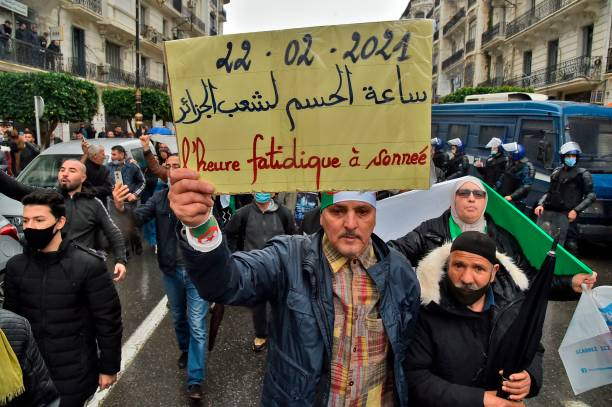 An Algerian man holds a placard during a demonstration in the capital Algiers on February 22 marking the second anniversary of the country's...