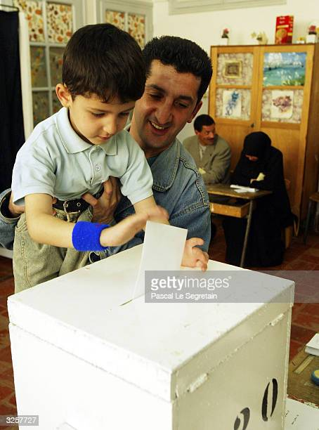An Algerian man lets his son cast his vote in a presidential election April 8 2004 in Algiers Algeria President Abdelaziz Bouteflika is considered...