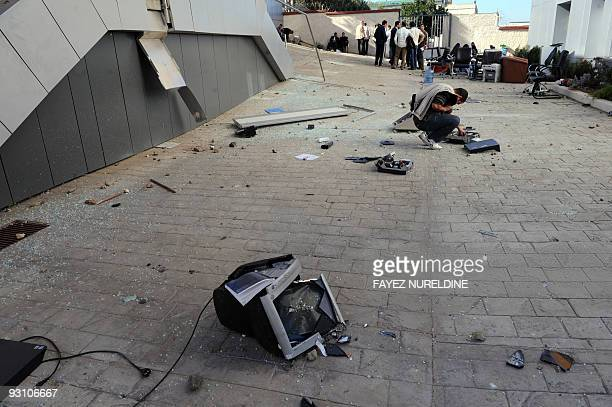 An Algerian man looks at broken material outside of the damaged main offices of mobile telephone company Djeezy part of the Egyptian...