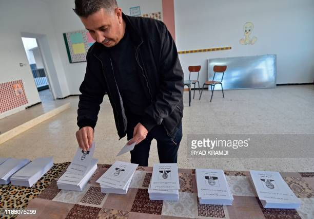 An Algerian man prepares to cast his vote during the presidential election on December 12 2019 at a polling station in Algiers Five candidates are...