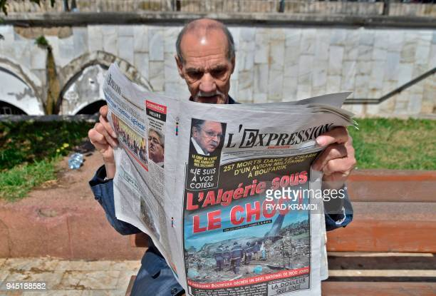 An Algerian man reads a newspaper in the capital Algiers on April 12 2018 headlining a military plane crash in which 257 people were killed Algeria...