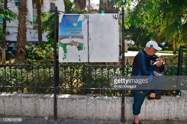 An Algerian man stands next to defaced campaign billboards ahead of the referendum in November which will vote constitutional reforms, on October 22,...