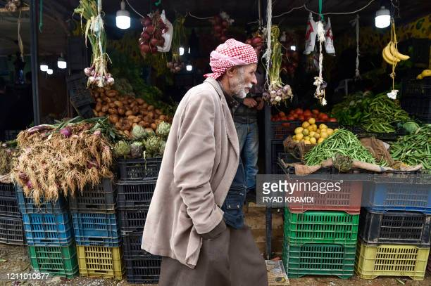 An Algerian man walks by a greengrocer's stall on the second day of the Muslim holy month of Ramadan in a market of the Khraicia district 20km south...