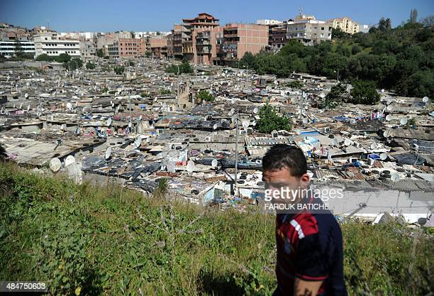 An Algerian man walks on a ridge overlooking the shantytown of elWiam in the Djasr Kasentina Wilaya in the capital Algiers on April 9 2014 Corruption...