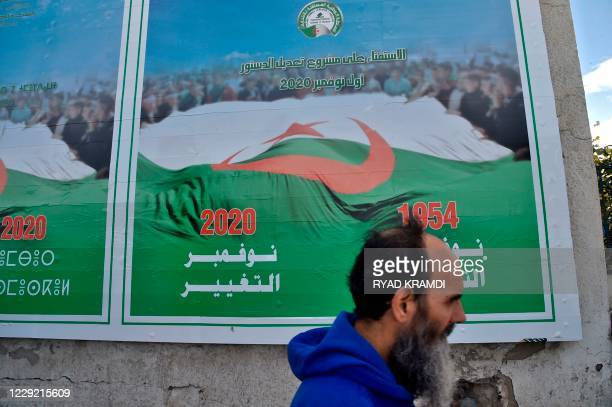 An Algerian man walks past campaign billboards ahead of the referendum in November which will vote constitutional reforms, on October 22, 2020 in...