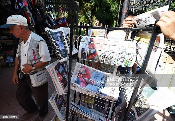 An Algerian man walks past newspapers displaying pictures and headlines denouncing the beheading of Frenchman Herve Gourdel by Jihadists linked to...