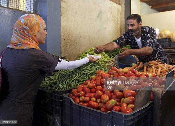 An Algerian market vendor sells vegetables to a woman at a popular market in Ain Benian suburb on August 21 2009 in Algiers before the start of...
