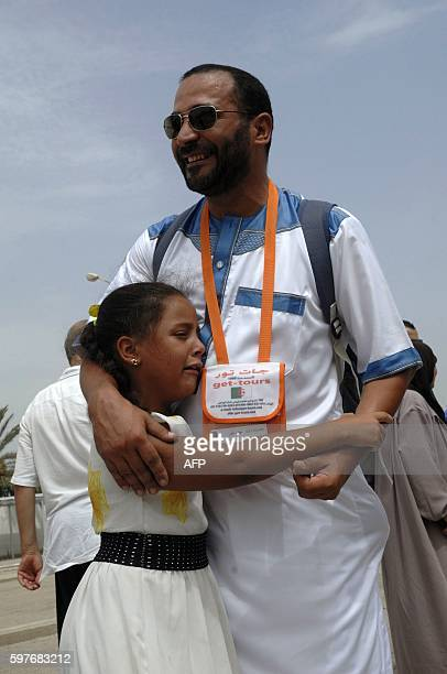 An Algerian pilgrim receives a hug from his daughter at Algiers airport on August 29 ahead of his departure to the annual Hajj pilgrimage in the...