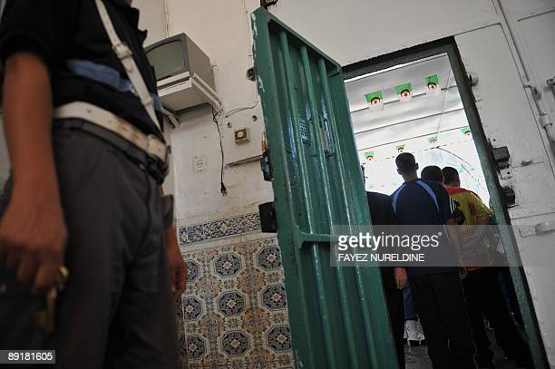 An Algerian policeman guards prisoners taking part in a marathon on July 22 2009 during a high school graduation ceremony at the AlHarach prison in...