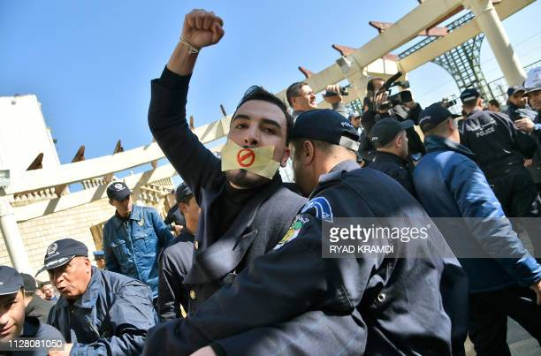 TOPSHOT An Algerian policeman restrains a protester participating in a rally organised by journalists against alleged censorship of coverage of...