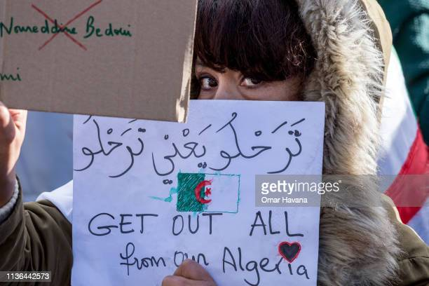 An Algerian protester holds a sign against Algerian President Abdelaziz Bouteflika during a demonstration on March 17 2019 in Paris France Close to...