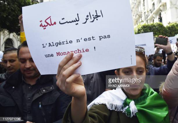 An Algerian protester holds a sign which reads in Arabic and French Algeria is not a monarchy during demonstrations in the capital Algiers against...