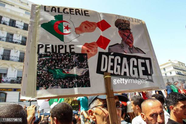An Algerian protester holds up a sign showing army chief Ahmed Gaid Salah in military uniform next to hands waving football red cards to him and...
