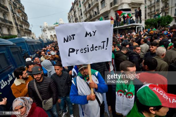 An Algerian protester lifts a placard in the capital Algiers on December 13 as he takes part in a demonstration to reject the results of the...