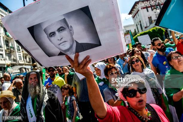 An Algerian protester marches with a sign showing the portrait of political activist Kamel Eddine Fekhar who died days earlier during a demonstration...