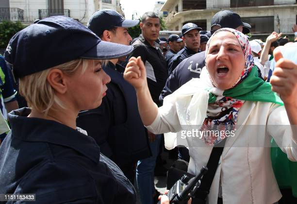 An Algerian protester shouts antisystem slogans as riot police stand guard during the weekly Friday demonstration in the capital Algiers on June 21...