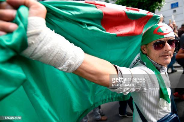 An Algerian protester waves national flag in the centre of the capital Algiers as anti-government demonstrations continue on November 5, 2019. -...
