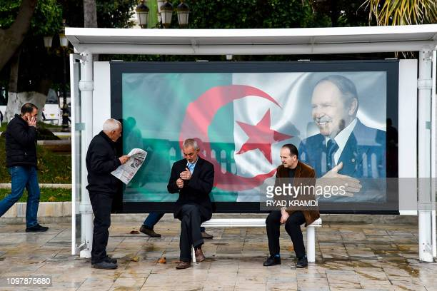 An Algerian reads a newspaper at a bus station next to a banner showing the Algerian flag with a portrait of President Abdelaziz Bouteflika in the...