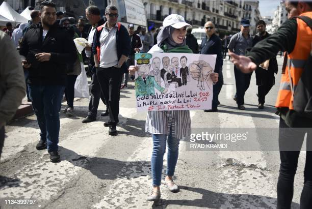 An Algerian student holds a placard as she takes part in a demonstration against the current government in the capital Algiers on April 2 2019 The...