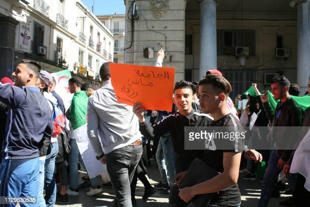 An Algerian student holds a placard during a protest against their ailing president's bid for a fifth term in power in the northeastern city of...
