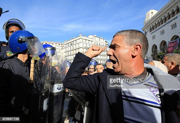 An Algerian trade unionist shouts slogans as they gather outside the People's National Assembly bulding in the capital Algiers on November 27 to...