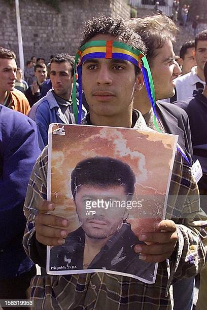 An Algerian waves a portrait of late Kabyle singer Matoub Lounes who was killed two years ago in a terrorist attacks as he gathers with some 5000...