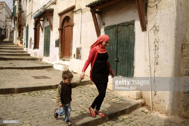 An Algerian woman and her child walk in the old part of the capital Algiers known as the Casbah on April 16 2014 Algerians weighed their options...
