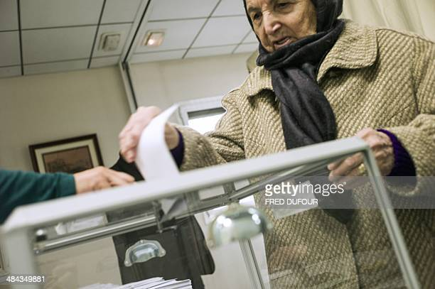An Algerian woman casts her ballot at a polling station in the Algerian Embassy on April 12 2014 in Paris Algeria's Abdelaziz Bouteflika who is...