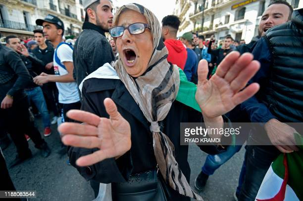 TOPSHOT An Algerian woman chants slogans as she takes part in an antigovernment demonstration in the capital Algiers on December 12 2019 during the...
