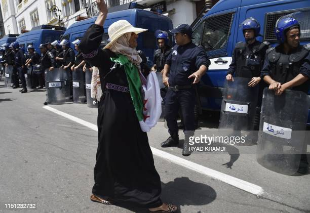 An Algerian woman draped in the national flag chants slogans as she walks past members of the security forces during the weekly Friday demonstration...