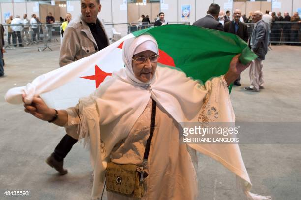 An Algerian woman holding a flag of Algeria over her shoulders prepares to vote for the Algerian presidential elections at a polling station in the...