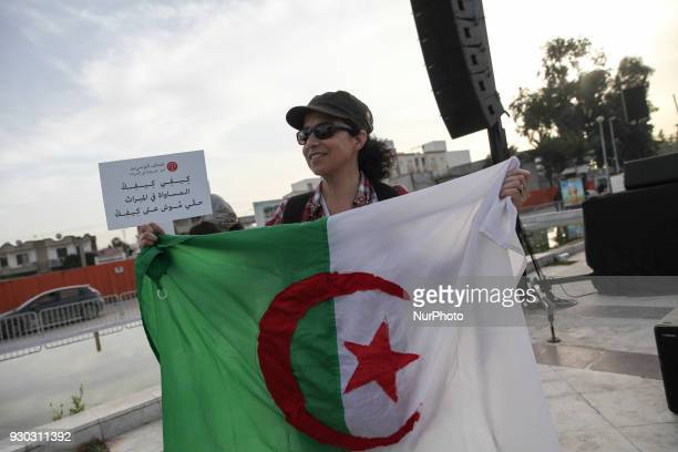 An Algerian woman holds the flag of Algeria during a march held in Tunis Tunisia to call for equal inheritance rights and gender equality on March 10...
