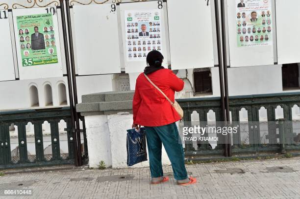 An Algerian woman looks at electorial campaign posters for the upcoming legislative elections in Algiers' Martyrs Square as the official start of...