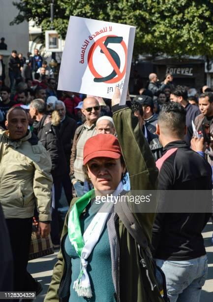 An Algerian woman marches with a sign during a protest rally against ailing President Abdelaziz Bouteflika's bid for a fifth term in power in the...