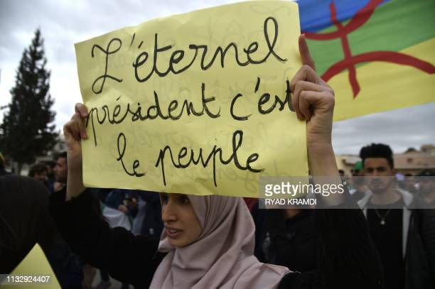 TOPSHOT An Algerian woman raises a placard during a demonstration against President Abdelaziz Bouteflika in the city of Bejaia some 220 km east of...