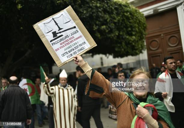 An Algerian woman raises placard as she takes part in an antigovernment demonstration on April 5 2019 in the capital Algiers 'Prosecutors and judges...