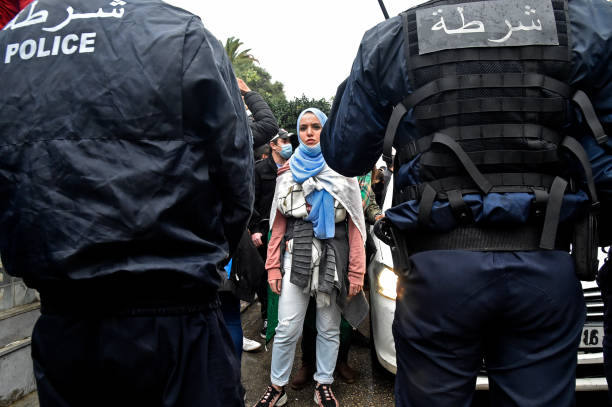 An Algerian woman stands in front of policemen during a demonstration in the capital Algiers on February 22 marking the second anniversary of the...