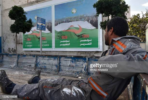 An Algerian worker looks at campaign billboards ahead of the referendum in November which will vote constitutional reforms, on October 22, 2020 in...