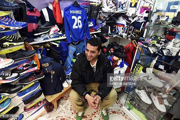An Algerian young man sits at a sports shop in front of a shirt of English club Leicester City's midfielder Riyad Mahrez on February 18 2016 in the...