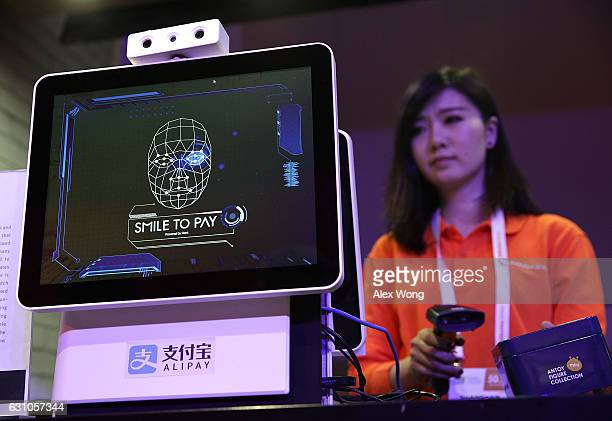 An Alibaba employee demonstrates 'Smile to Pay' an automatic payment system that authorize payment via facial recognition at the Alibaba booth during...