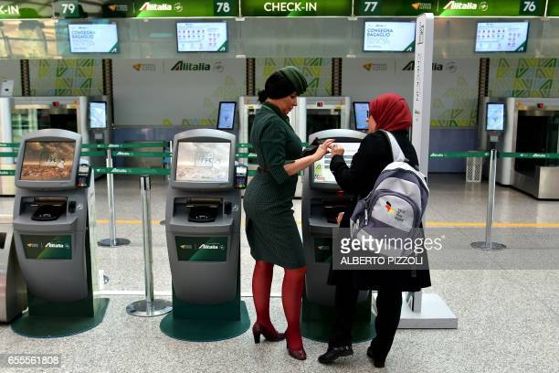 An Alitalia air carrier employee helps a passenger at the checkin desk on March 20 2017 at Rome's Fiumicino airport Air traffic in Italy was being...
