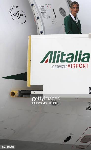 An Alitalia air hostess stands at the entrance of a plane at Fiumicino Airport on September 12 2008 Italian ANSA news agency reported that Italian...
