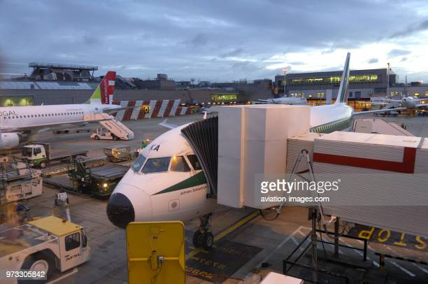 an Alitalia Airbus A320200 parked at the terminal with jetway extended and an Air Portugal A320200 parked behind with airstairs