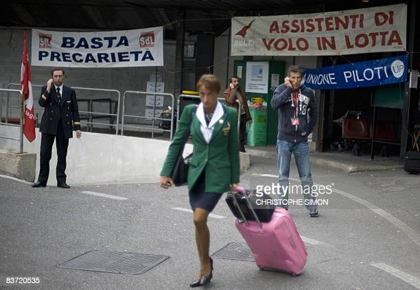 An Alitalia airhostess walks near banners reading 'stop precarious work' and 'flight assistance fighting' outside Rome's Fiumicino airport on...