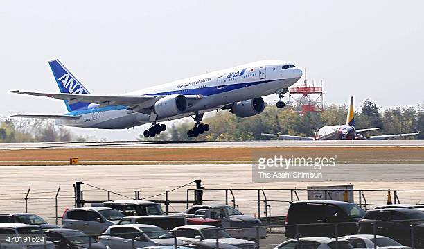 An All Nippon Airways aircraft takes off while the damaged Asiana Airlines flight 162 remains off the runway at Hiroshima Airport on April 17 2015 in...