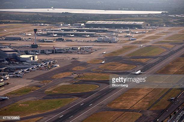 An All Nippon Airways Co aircraft right prepares to takeoff from the north runway at London Heathrow Airport as the British Airways Plc Terminal 5...