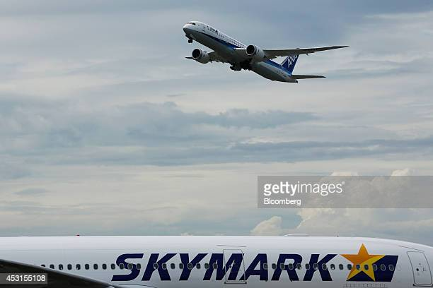 An All Nippon Airways Co Boeing Co 7879 Dreamliner aircraft flies over a Skymark Airlines Inc aircraft during take off at Haneda Airport in Tokyo...